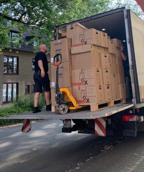Möbelpacker verladen eine Palette mit Umzugskartons in einen Möbelwagen
